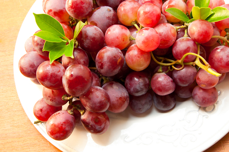 uvas: uvas rojas en un plato blanco Foto de archivo