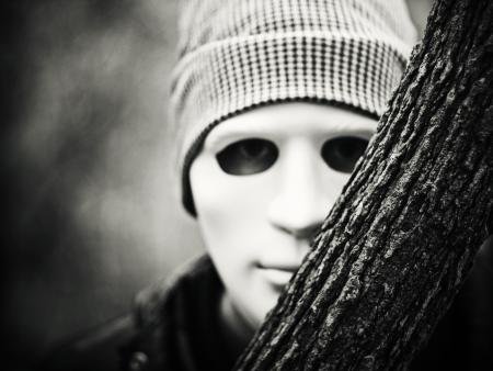 hombre con máscara blanca asomando detrás del árbol Foto de archivo