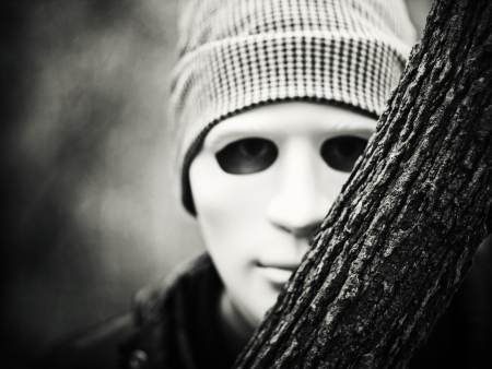 scary man: man with white mask peeking behind tree Stock Photo