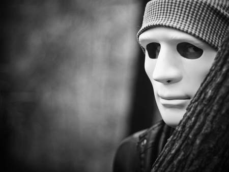 murderer: Man with white mask standing behind tree Stock Photo
