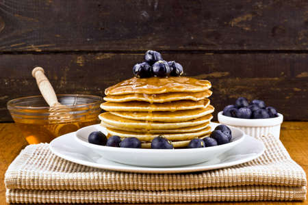 Stack of pancakes with fresh blueberry and honey  selective focus  photo