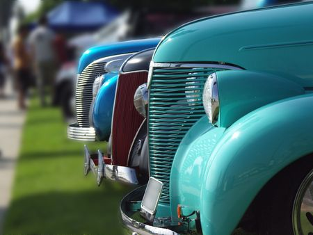 street rod: cars lined up at a vintage car show, with blurred background