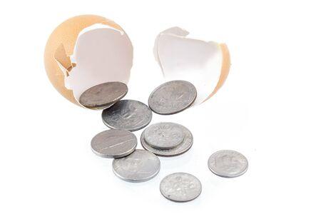 libra esterlina: Monedas  dinero proviene de huevo grieta en el fondo blanco aislado