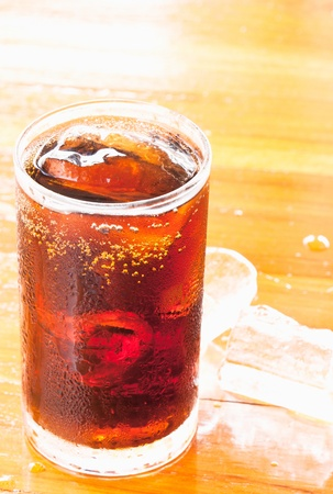 glass of cola with ice on the wooden floor photo