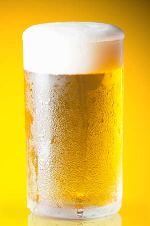 Beer glass with froth over yellow background