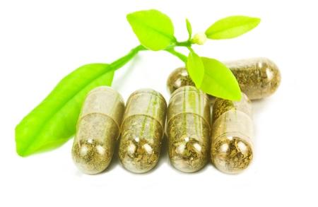 recetas medicas: píldoras a base de hierbas medicinales con plantas verdes sobre fondo blanco Foto de archivo