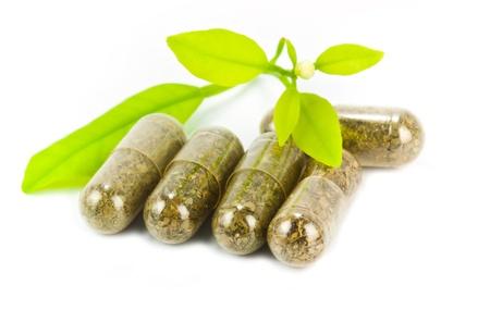 medicina natural: p�ldoras a base de hierbas medicinales con plantas verdes sobre fondo blanco Foto de archivo