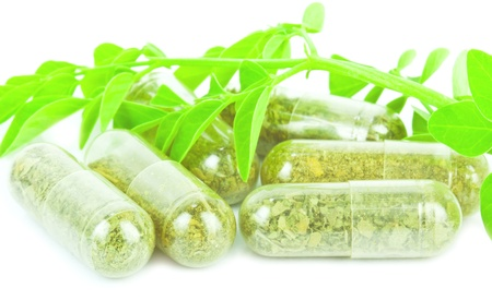 herbal medicine pills with green plant on white background