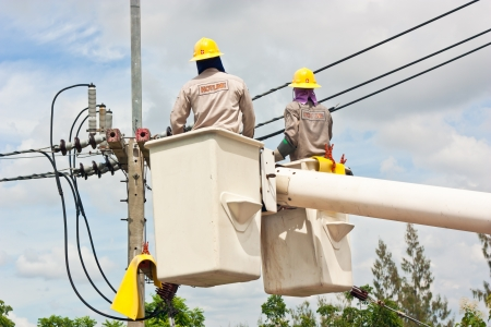 Electrical worker in a bucket fixes a problem with a power line  photo