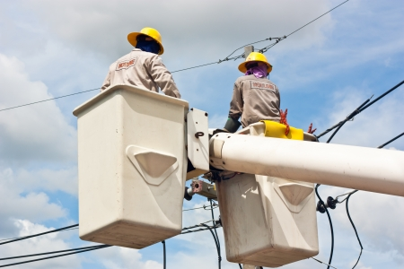 power cables: Electrical worker in a bucket fixes a problem with a power line