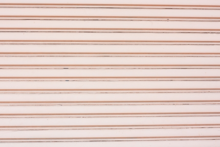 Old pink metal roller shutter use as background or textures photo