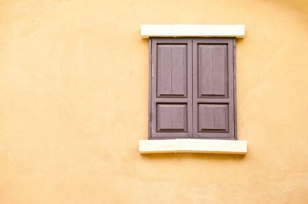 old wood windows on the yellow wall