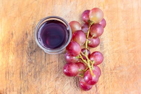 Verre de jus de raisins et de raisins sur le bois. Banque d'images - 62157513