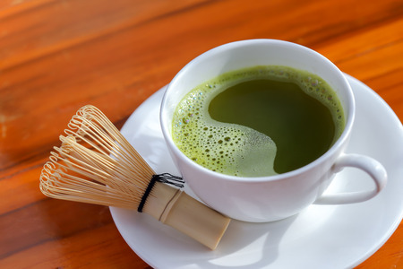 healthy green tea in cup and bamboo whisk