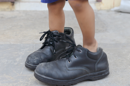 childs feet in large black shoes