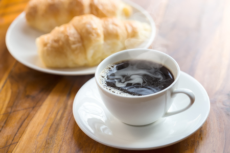 cup of hot black coffee with crispy fresh croissants Stock Photo