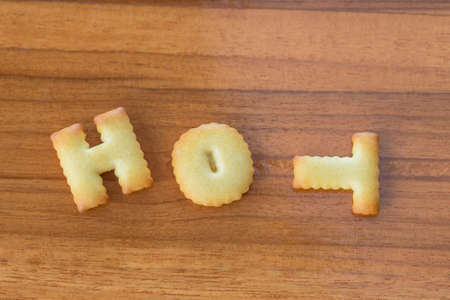 HOT alphabet biscuit on wooden table Stock Photo