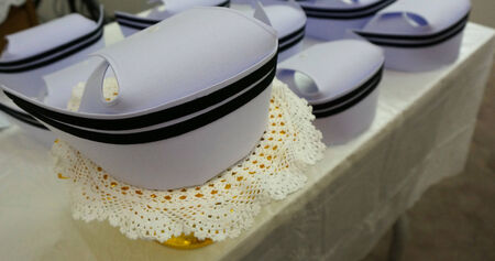 White nurses hat and a black stripe, Placed on a table that overed with a white tablecloth.                               photo