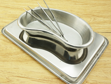 Two forceps put in Kidney-shaped bowl and placed on the tray            photo