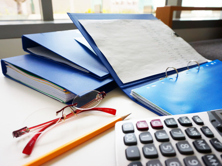 placed: Blue folders and other office equipment, such as calculators, pencil and glasses, placed on the desk