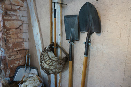 unearth: Farm equipment, gardening, resting against the wall behind the house, such as shovels, spades.