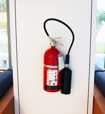 inflammable: Fire extinguisher has red color, use when  happens the fire, hang it on the wall in the visible area.                               Stock Photo