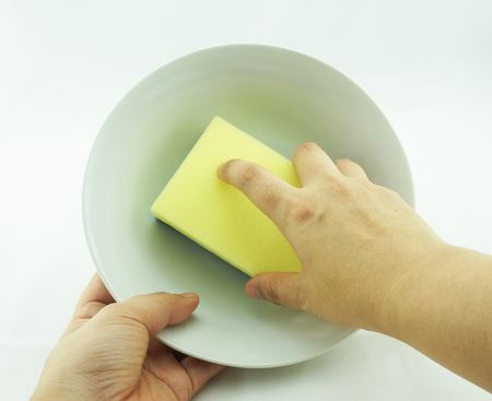 Womans hand, right hand holding dishwasher sponge and left hand holding bowl.                               photo