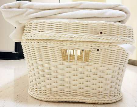 White basket with a lid. Used for clothes placed on the table in hotel.                                 photo