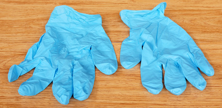 sterilized: A pair of blue medical gloves, placed on the brown wood.