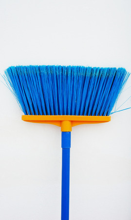 broom handle: Escoba azul de pl�stico, mango es de color azul, colocada contra la pared blanca de la casa.