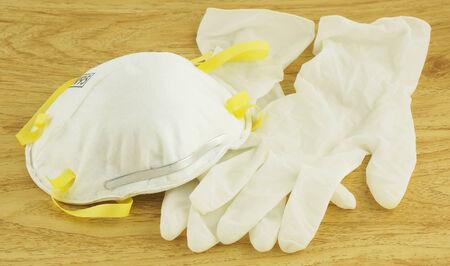 disease prevention: N95 m�scara blanca y guantes para la prevenci�n de enfermedades, colocado en el piso de madera.