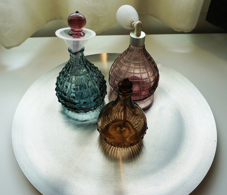 Perfume bottles made of glass, beautiful shape located on the tray.