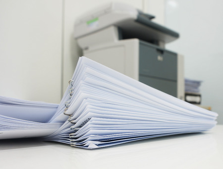 printer ink: The document has been printed, be set and arranged as pile in front of the copier at office.