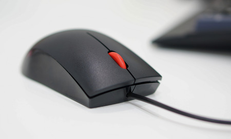 scrolling: Computer mouse has a black wire attached to the PC, scrolling button is red in the middle. Stock Photo