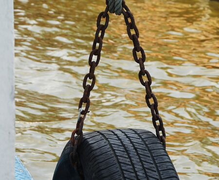 rustiness: Old rusty chains for hanging tire cushioning at ferry pier.