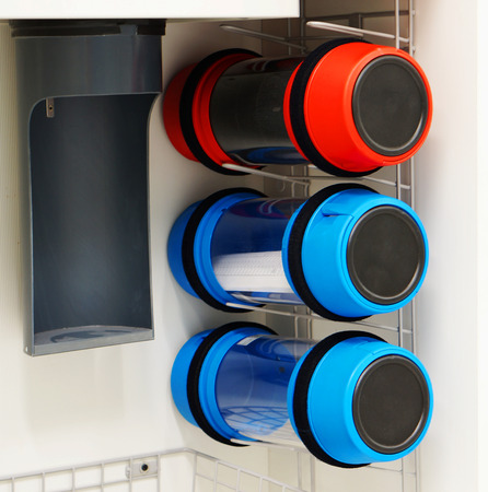Pneumatic tube transfer system station and a row of capsules attached to a building wall. Stock Photo