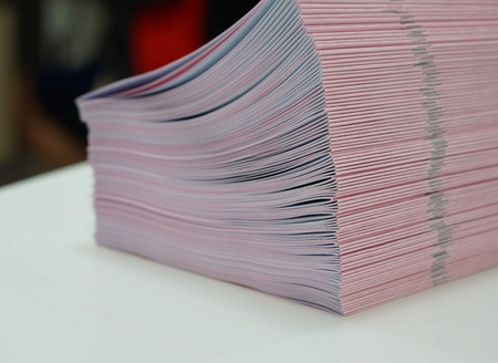handouts: Piles of pink handout papers placed on table at office. Stock Photo