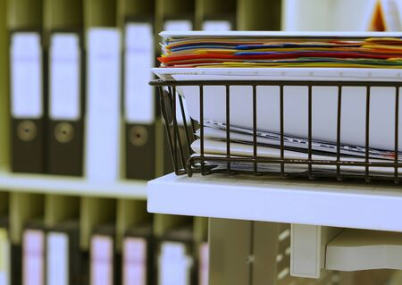 categorize: Many file of multicolored document in black basket at office.