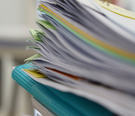 stack of papers: Pile of documents and blue file on desk at office.