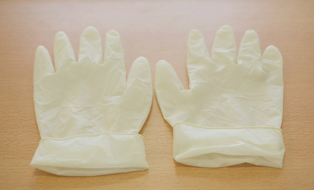 nurse gloves: Pair of latex medical gloves on wooden table at counter nurse. Stock Photo