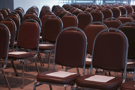 schoolroom: Empty classroom contained with brown chairs and document on top. Stock Photo