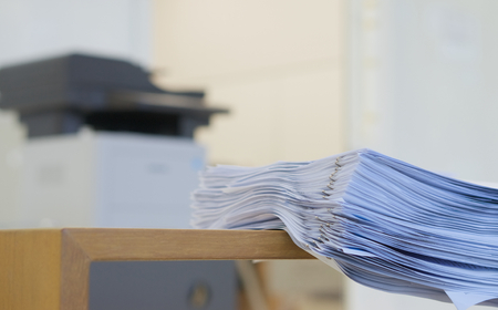 xerox: Stack of document is organized on desk after printing in office.