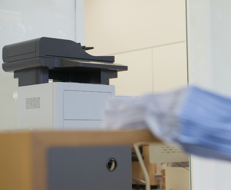 xerox: Printer for photocopy is placed in front of room in office.
