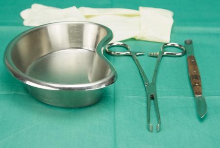 pinza quirúrgica y cuchillo colocan cerca de un tazón forma de riñón en tela verde. Foto de archivo