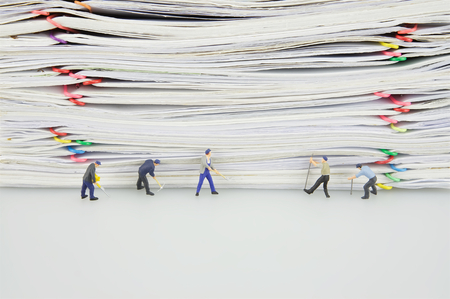 manuscript: Pile overload paper with colorful paperclip and miniature people are destroyed it on white background.