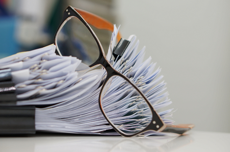 Unfinished document, stacks of paper files with clips on desk for report and glasses in the office at morning, Business offices concept on workplace background.