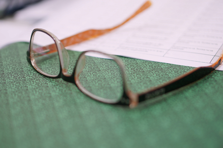 Close notebook, open one sheet and glasses on the office table at workplace, Business, finance, banking, loan, investment, taxes or accounting concept. Stock Photo