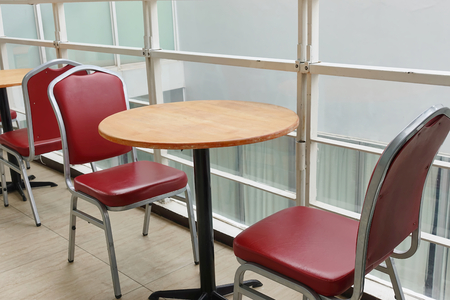 Empty of red chairs and round wooden tables outside cafeteria in hotel.