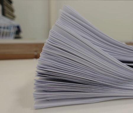 Stack of meeting paper on the table with blurred of office room interior background.