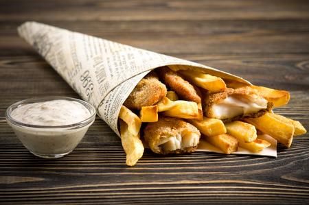 fish and chips: Virutas de pescado en la mesa de madera